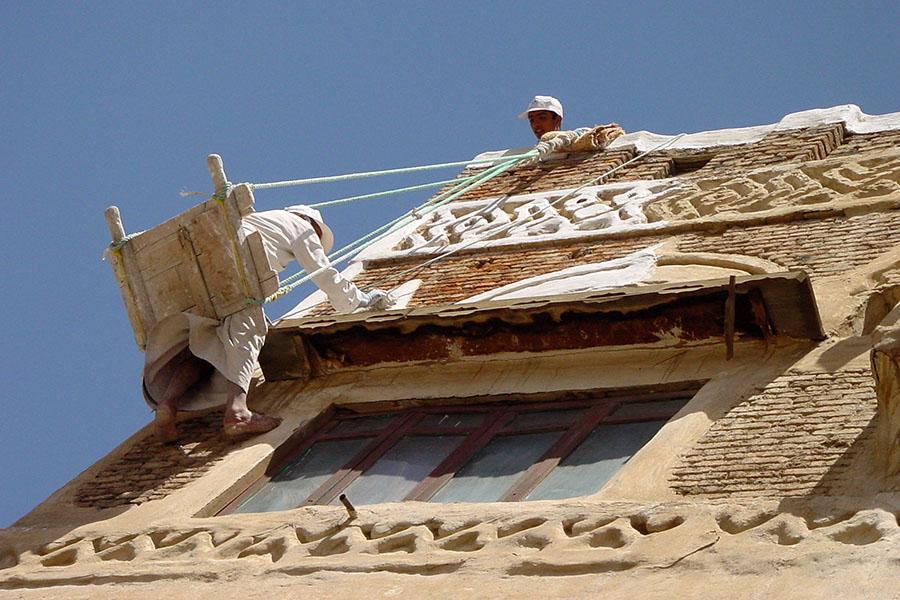 De muur van een gebouw in Sana'a verven