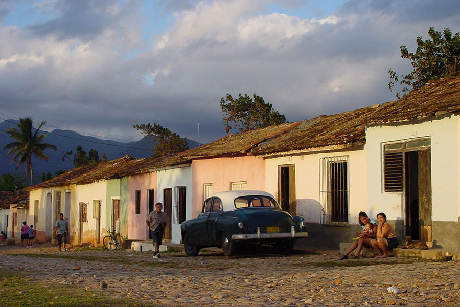 Street with Cubans and oldtimer in Cuba