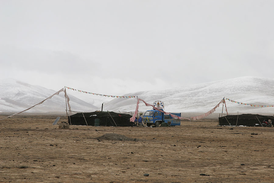 Nomad tent with small truck in snowy landscape of Qinghai province