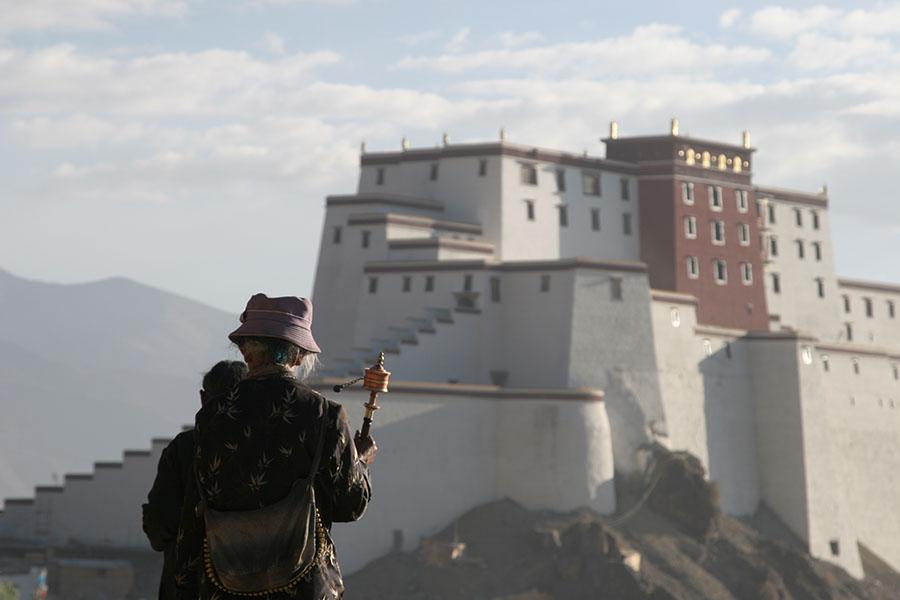 Pilgrims on their way around Tashilhunpo kora with Shigatse fortress in the background