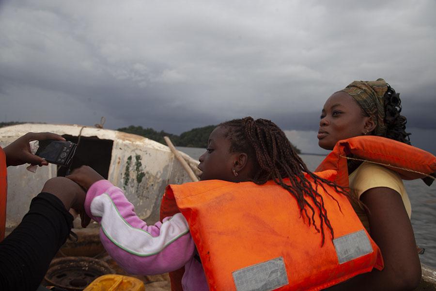 Moeder met meisje op het bootje naar Cogo