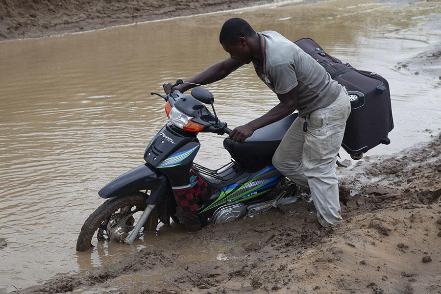 Een van de motorfiets rijders duwt zijn fiets door de diepe modder