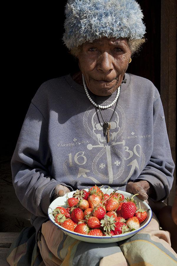 Oude vrouw met een schaal aardbeien