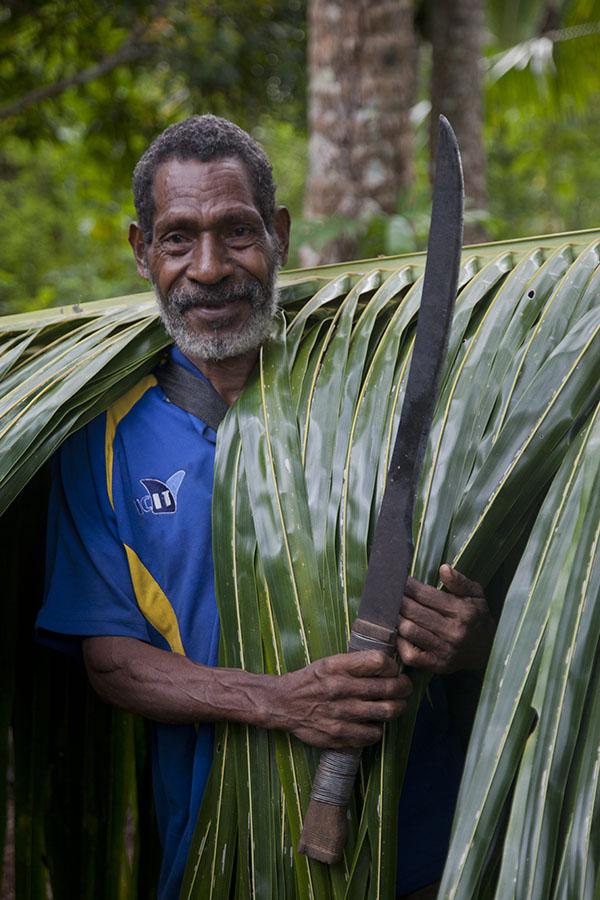 Papoea met machete en palmblad